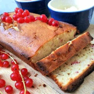 Redcurrant yoghurt loaf cake with fresh redcurrants on top, two slices cut out.