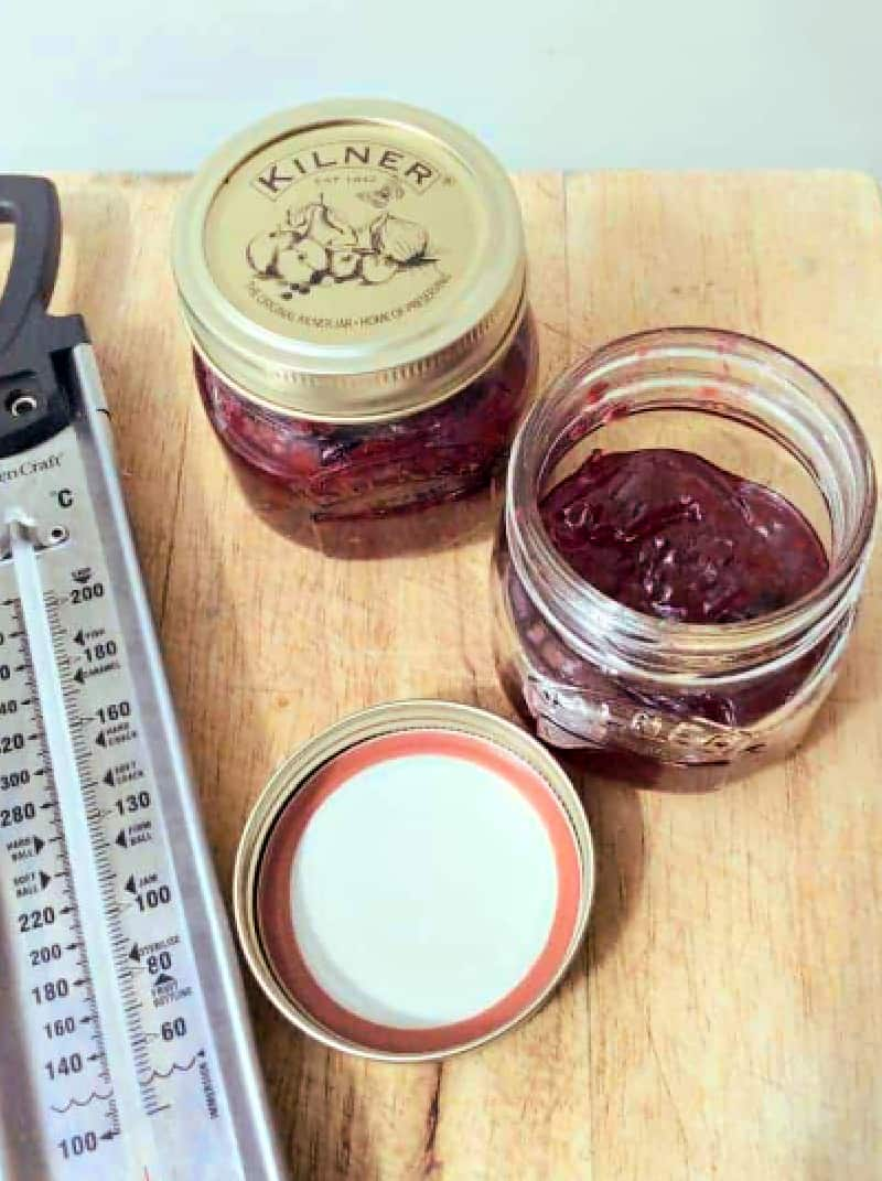 Jars of jam and sugar thermometer on a wooden board.