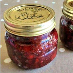 Close up of a small jar of red jam.