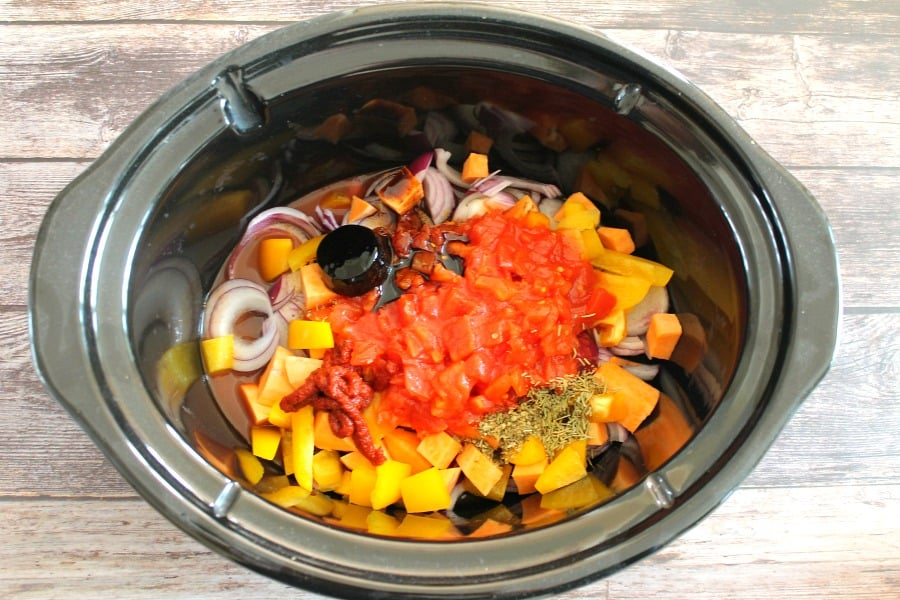 Vegetables with tinned tomatoes and stock pot in slow cooker pot.