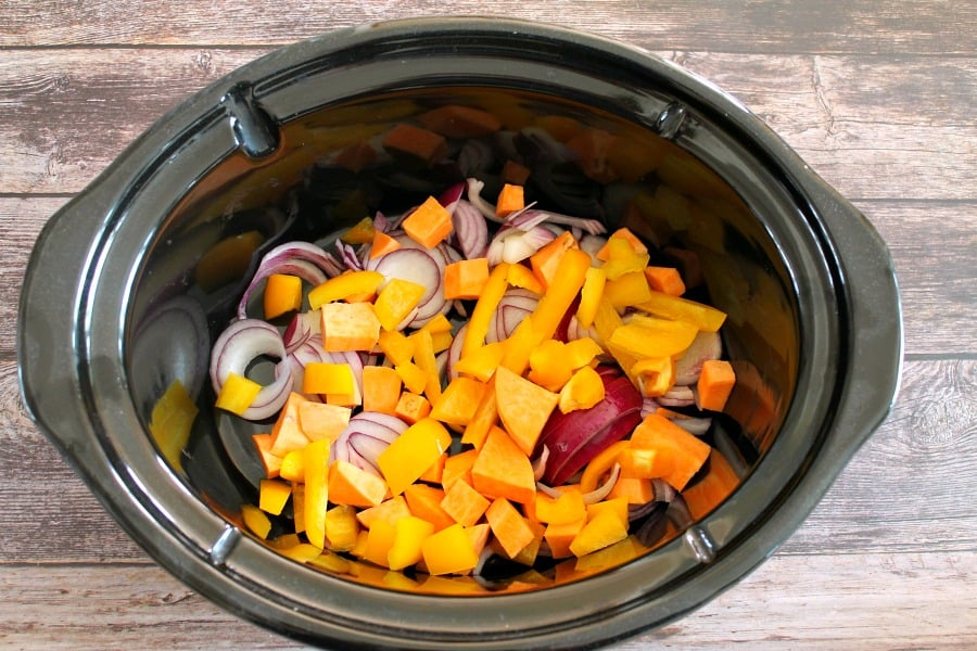 Vegetables in a slow cooker pot (carrot, onion, sweet potato, peppers).