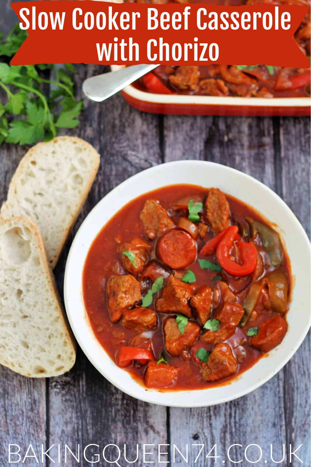 Bowl of beef casserole served with crusty bread on the side, with herbs and serving dish behind, with text overlay (slow cooker beef casserole with chorizo).