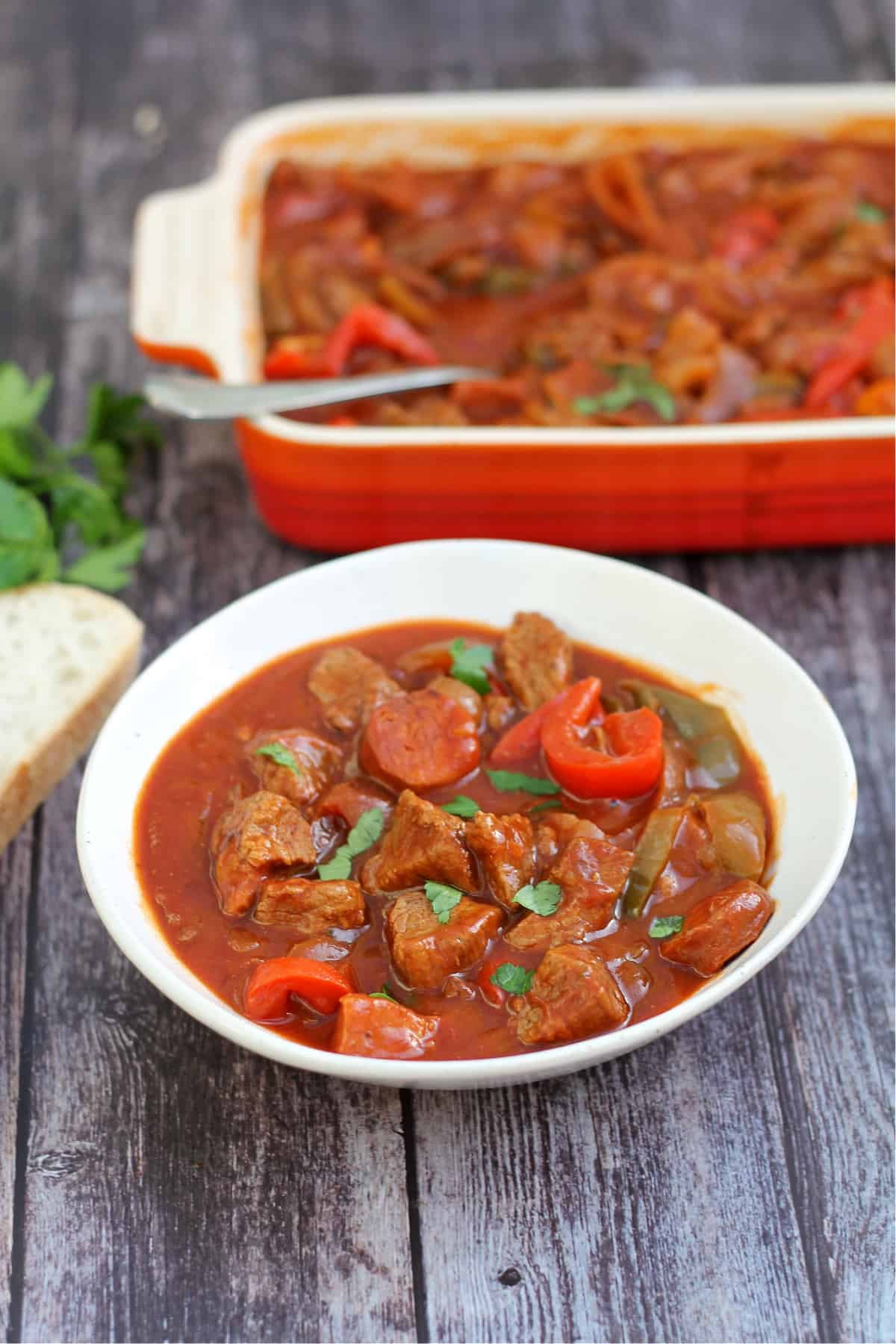 Bowl of beef stew with serving dish behind and bread to the side.
