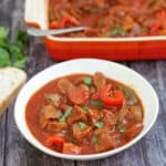 Bowl of beef casserole with bread on the side, with serving dish behind, with text overlay (slow cooker beef casserole).