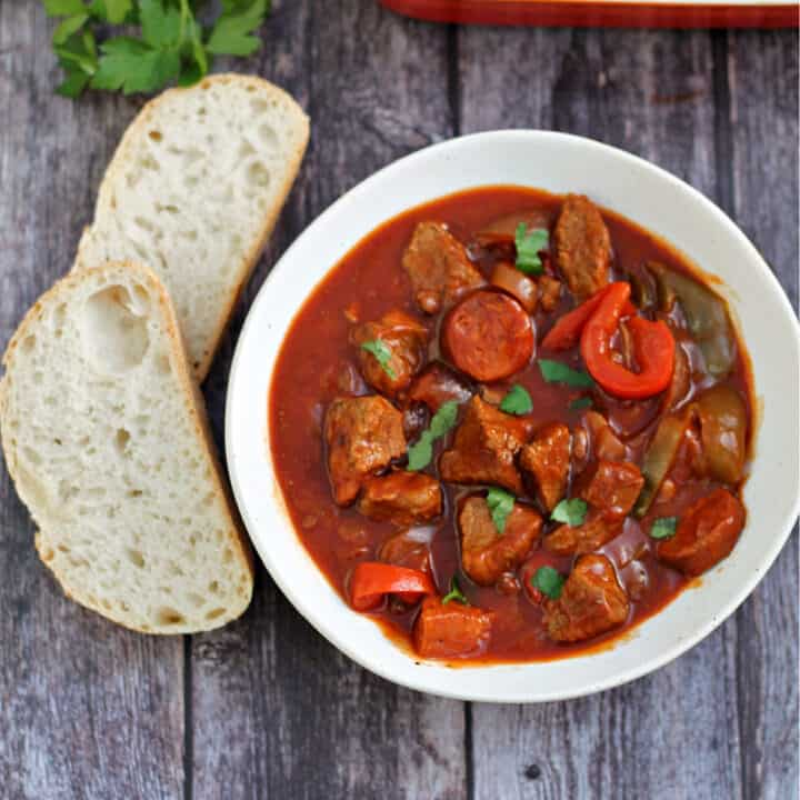 Bowl of beef casserole served with crusty bread on the side, with herbs and serving dish behind.
