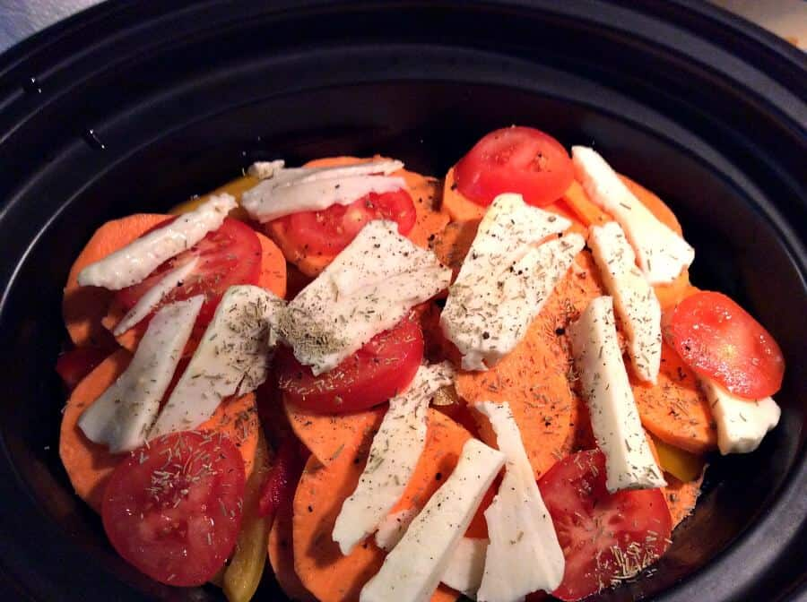 Slow cooker halloumi bake - the top layer of sweet potato is topped with tomato, herbs and halloumi