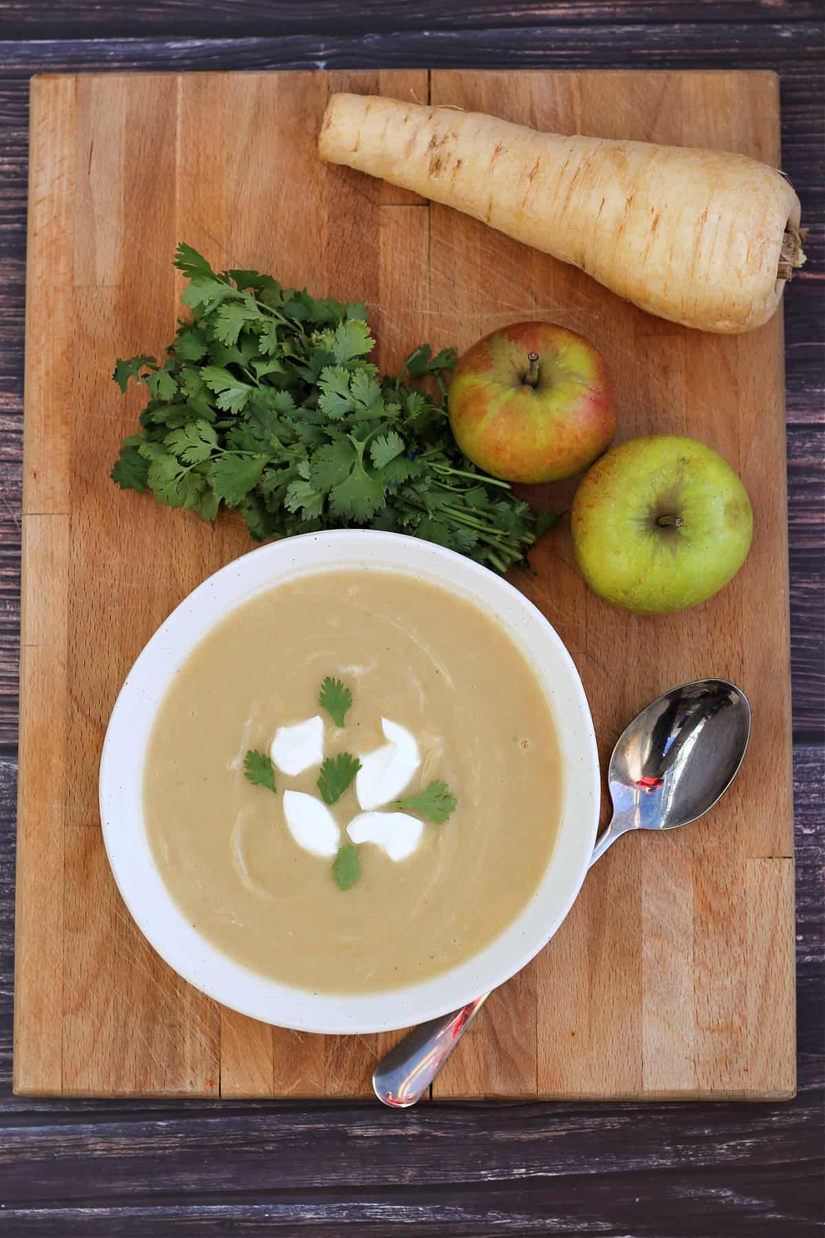 Bowl of soup on a wooden board with parsnip, apples and herbs behind.