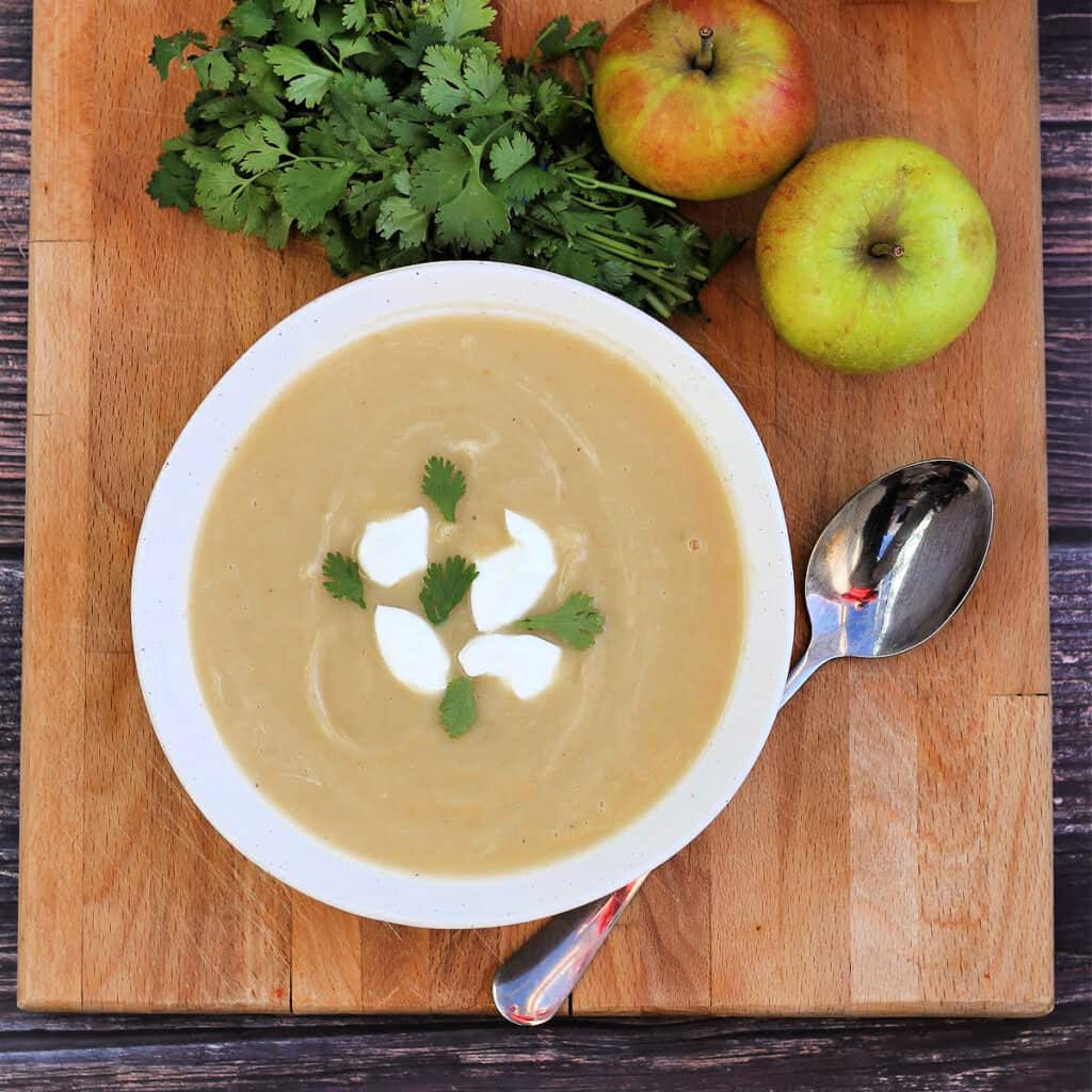 View from above of bowl of soup on wooden board with apples and herbs beside.
