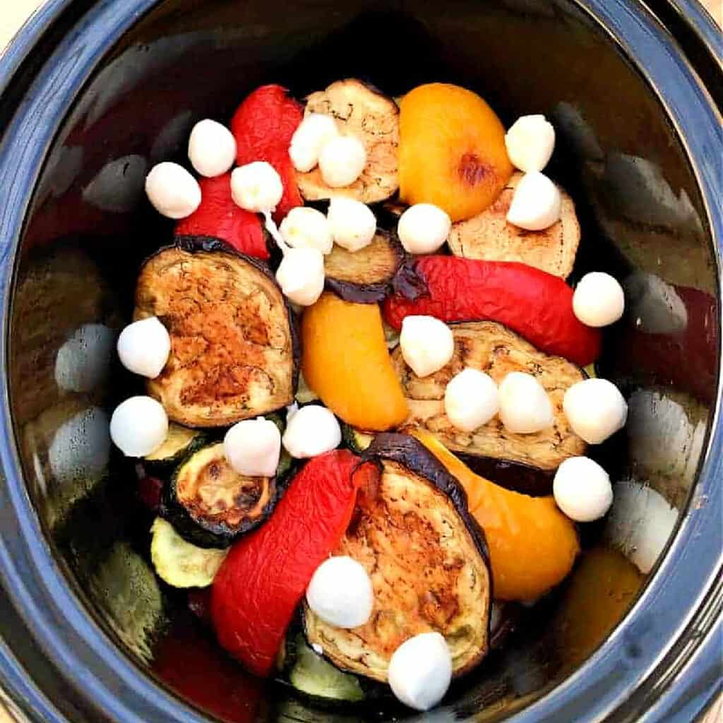 Slices of pepper, aubergine and courgette with mozzarella pearls on top, in pot.