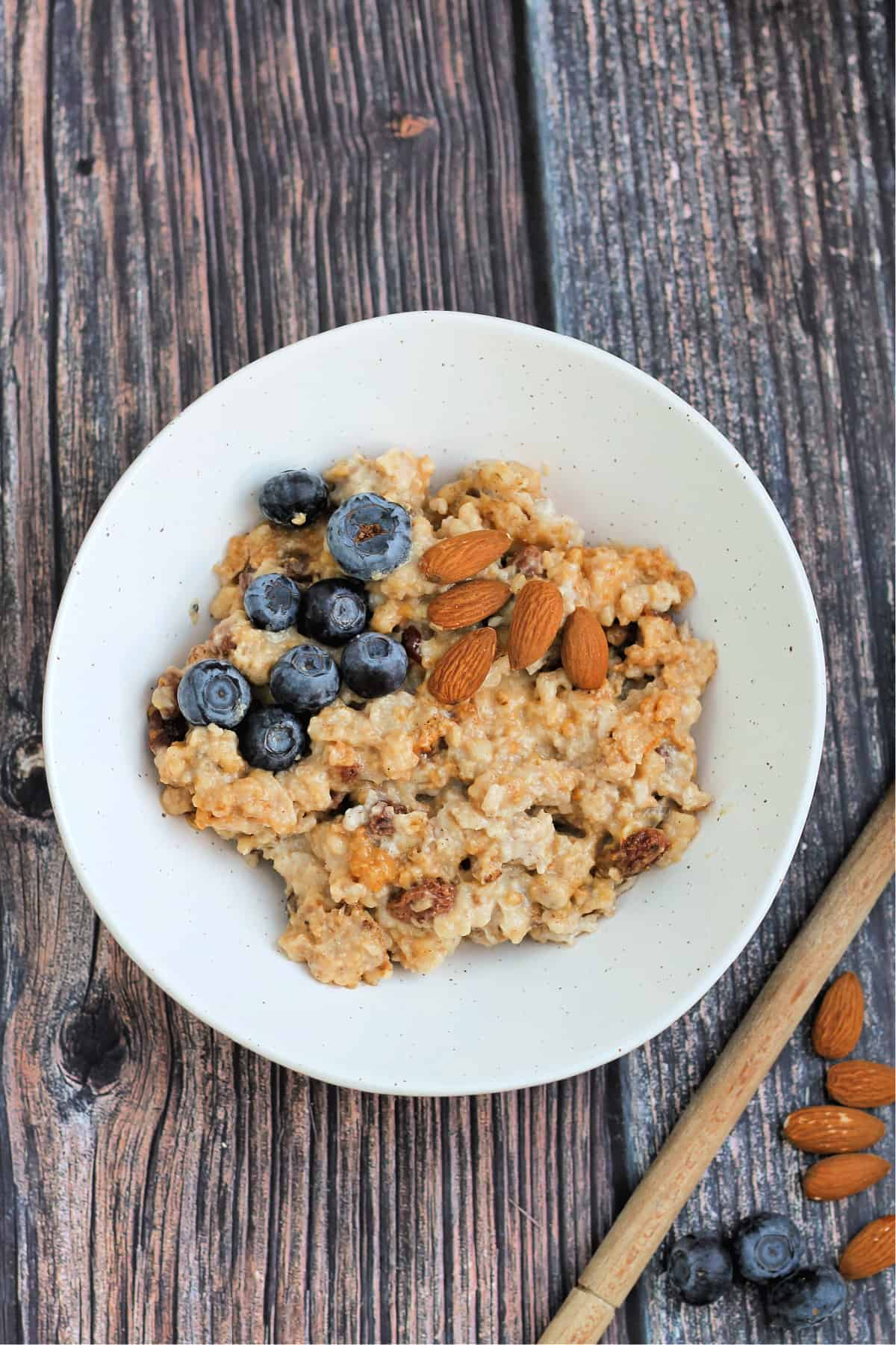 A white bowl of porridge/oatmeal with almonds and blueberries on top.