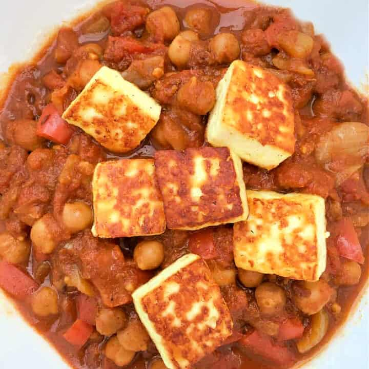 Close up of curry in a white bowl with paneer cheese cubes.