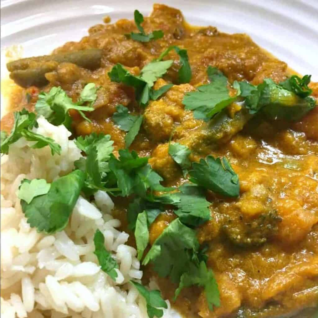 Close up of curry on a white plate garnished with chopped coriander.