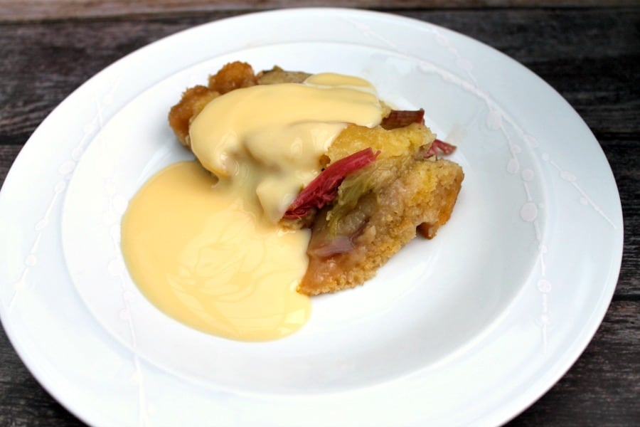 Slow cooker rhubarb cobbler serving on white plate with custard