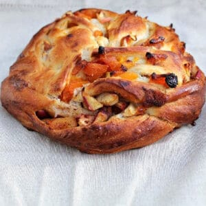 Couronne (crown) bread filled with apricots and dried fruit, on a grey fabric background.