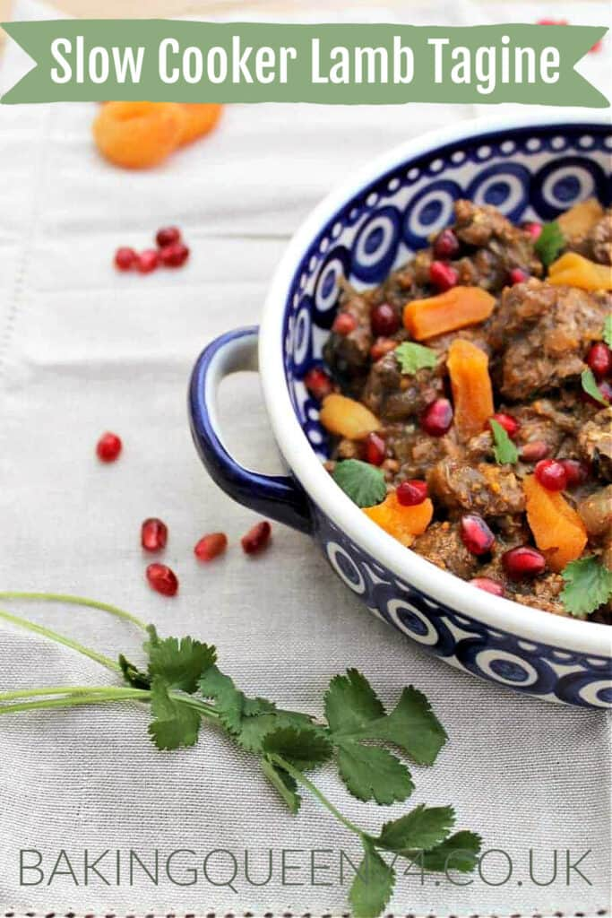 Lamb tagine served in a blue and white dish, with apricots, pomegranate seeds and flatleaf parsley, with text overlay (slow cooker lamb tagine).