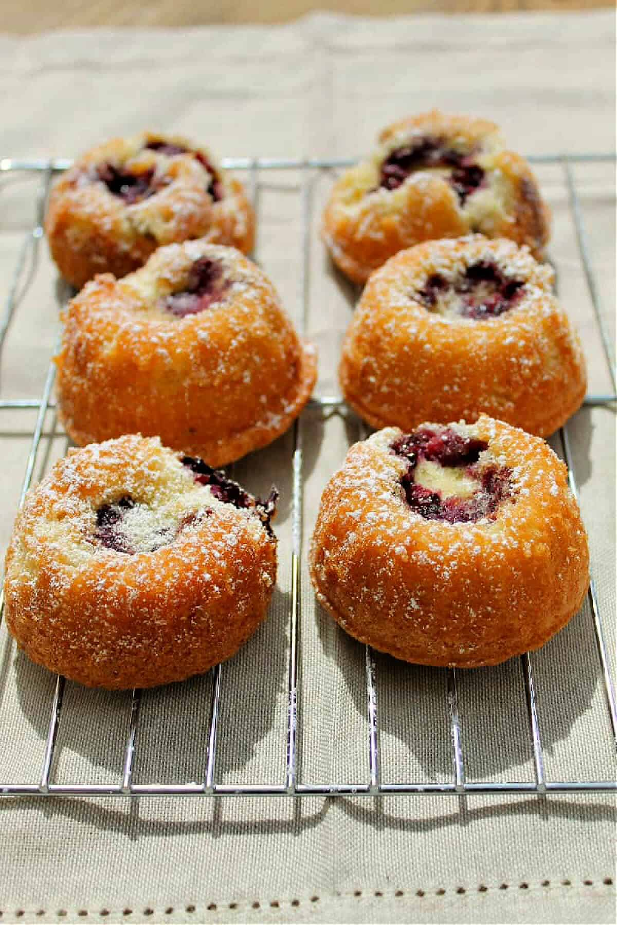 Six small cakes with blackberry filling on a metal cooling rack.