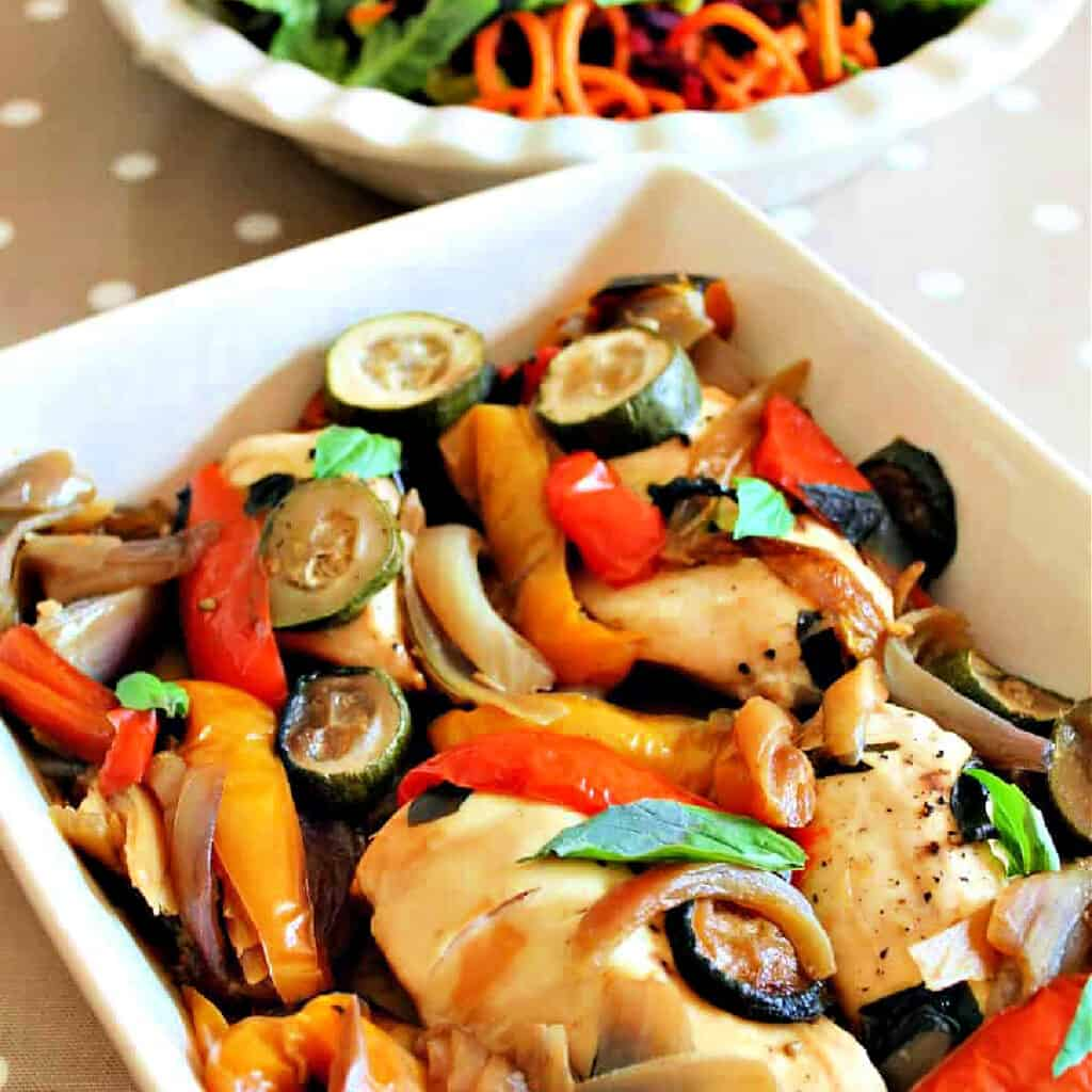 White serving dish of chicken with roasted veg, bowl of salad behind.