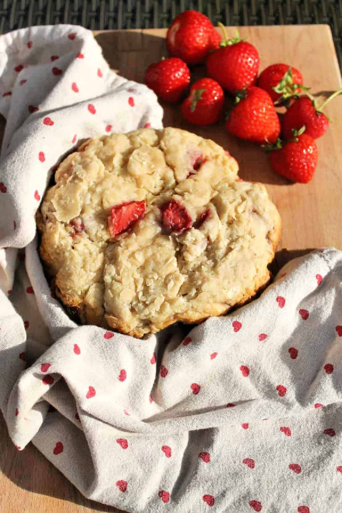 Large scone with strawberries on a board on a tea towel, with strawberries to the side.