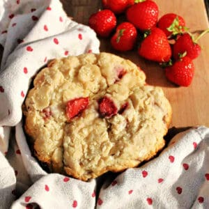 Close up of a large strawberry scone cake on wooden board, strawberries on the side.