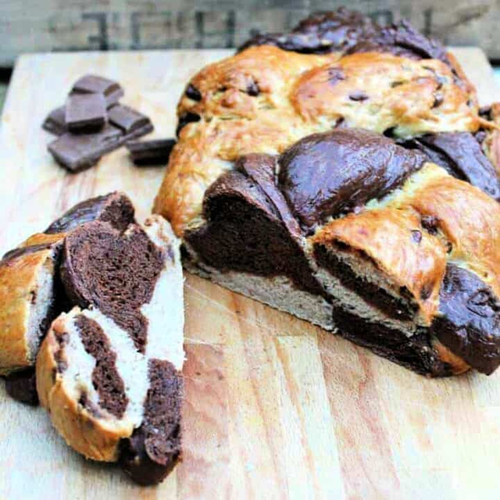 Two-tone dark brown and white challah bread sliced open on a cutting board.