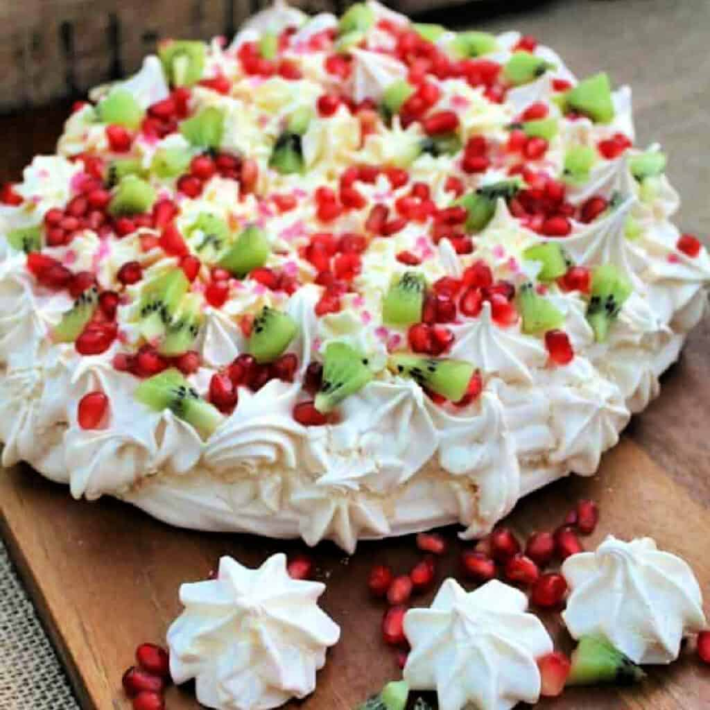 Festive pavlova topped with red and green fruit, with piped decoration.