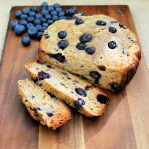 Banana and blueberry bread on wooden board, two slices cut.