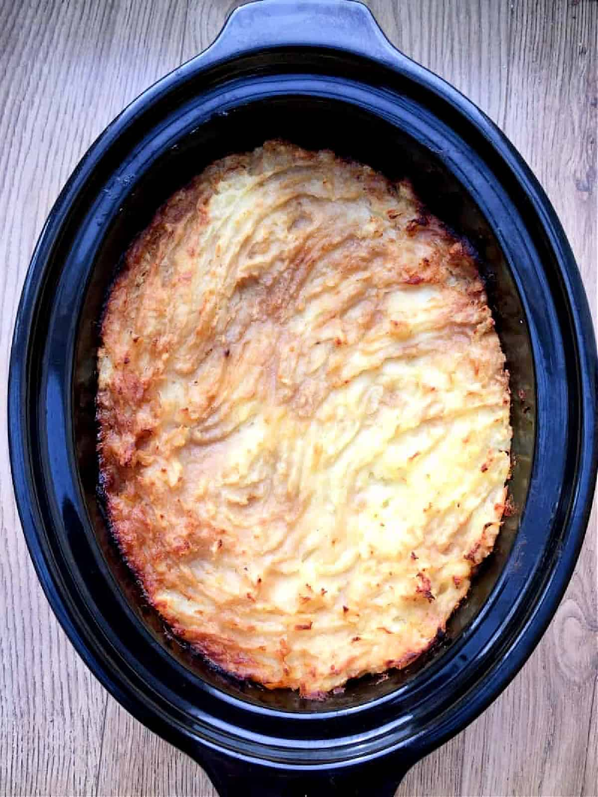 View of cottage pie with browned top in slow cooker pot.