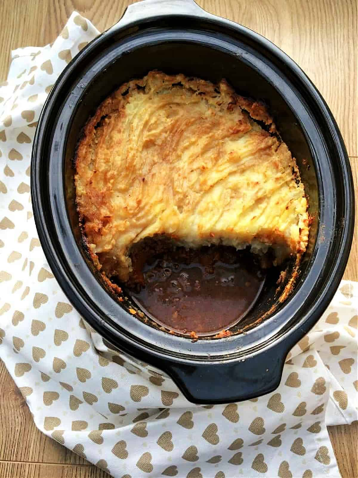 Overhead view of cottage pie with mashed potato topping in slow cooker pot.