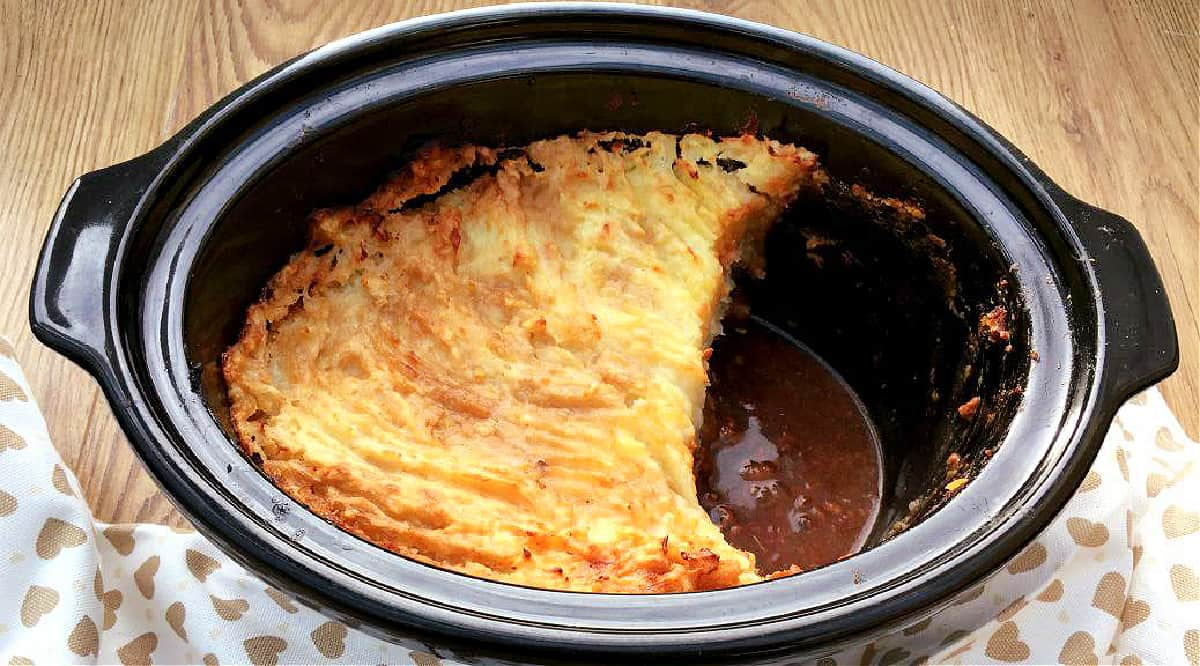Cottage pie in slow cooker pot, some portions already removed.