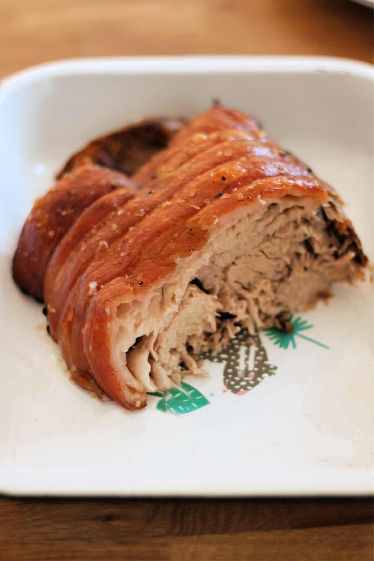 Roast pork joint in a serving dish, showing the soft meat inside.