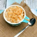 Bowl of rice pudding with spoon on a piece of hessian.