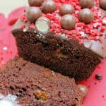 Close up of sliced open chocolate cake topped with Maltesers.