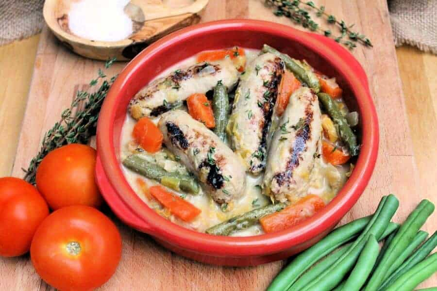 Red bowl with sausages and carrots, with tomatoes and green beans around it.
