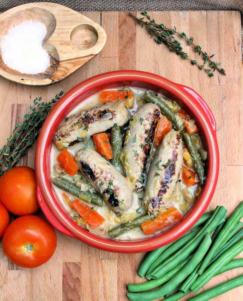 View from above of red bowl with sausages and carrots, with tomatoes, bowl of salt, herbs and green beans around it.