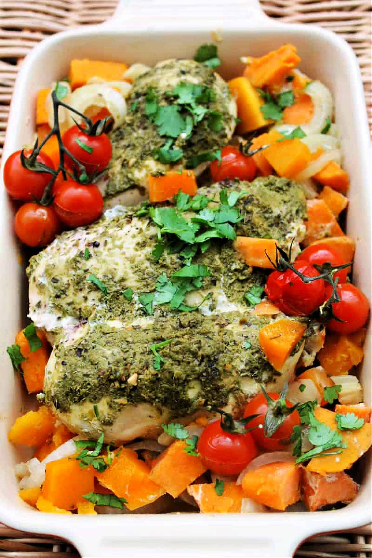 Serving dish of chicken with pesto and vegetables.
