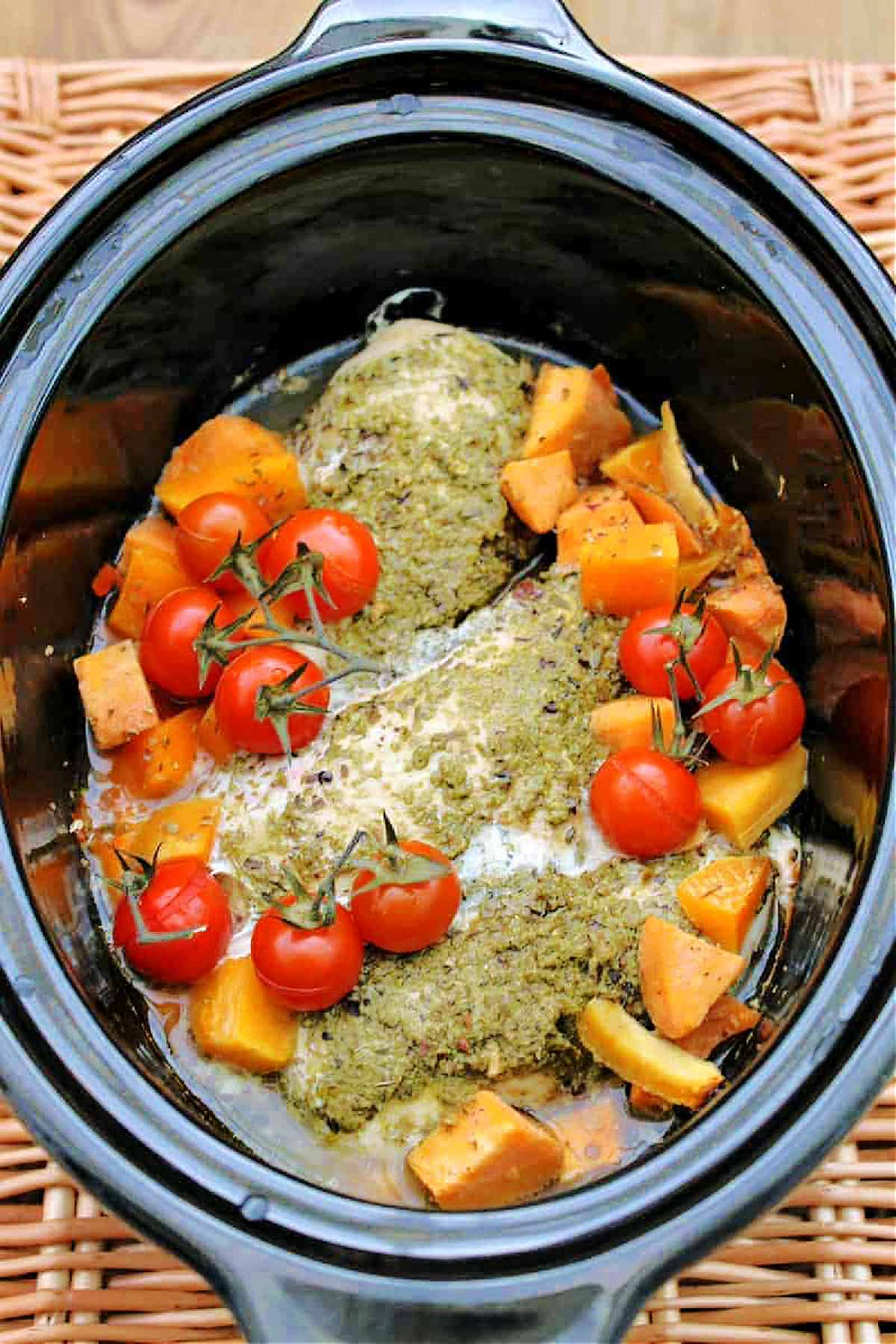 Slow cooker full of chicken with pesto on top, tomatoes and sweet potato chunks.