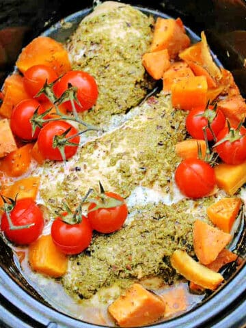 Slow cooker pot with chicken with pesto on top, tomatoes and sweet potato chunks.