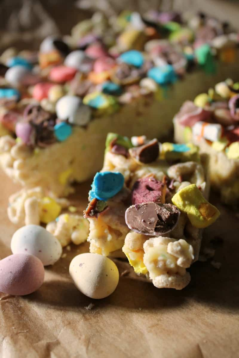 Close up of one square of the slice topped with mini eggs and lucky charms.