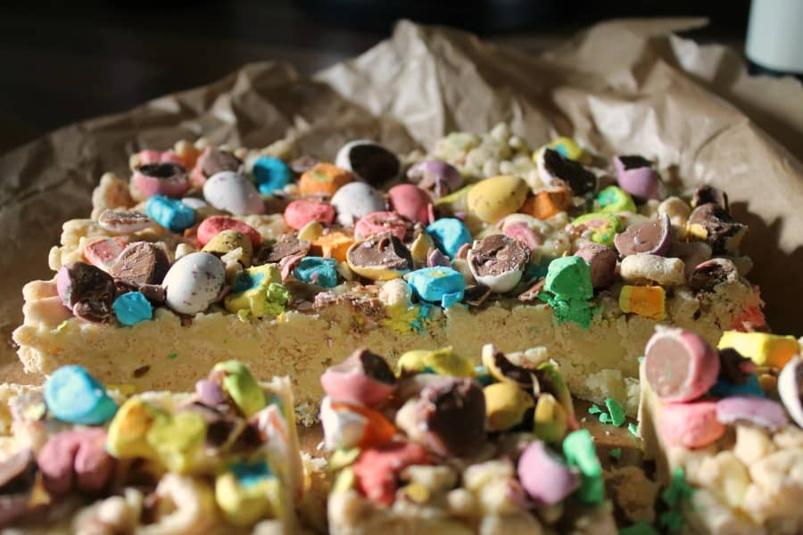 Close up of the top of the white chocolate slice with lots of colourful Mini eggs and Lucky Charms
