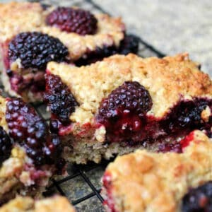 Squares of blackberry traybake on a cooling rack.
