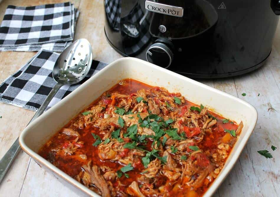 Serving up the paprika pork goulash from a serving bowl next to the crockpot