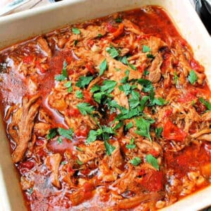 Shredded pork with peppers in a white serving dish.