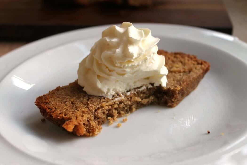 Slow cooker sticky ginger cake with whipped cream on top and a bite taken out