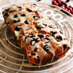 Close up of fruit-studded cranberry cake on cooling rack, with dripping icing.