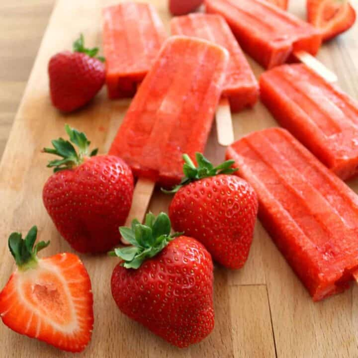 Close up of strawberry ice lollies and strawberries on a wooden board.