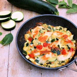 Frittata in a frying pan, with sliced courgettes and herbs around.