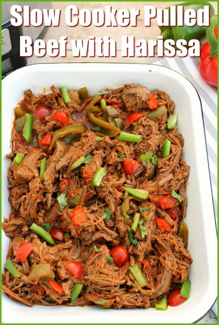 """Pulled beef in a white serving dish with text overlay """"Slow cooker pulled beef with harissa""""."""