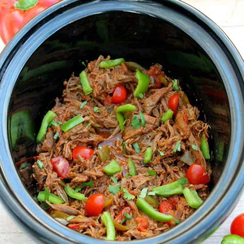 Shredded beef in the slow cooker pot with tomatoes and green peppers.