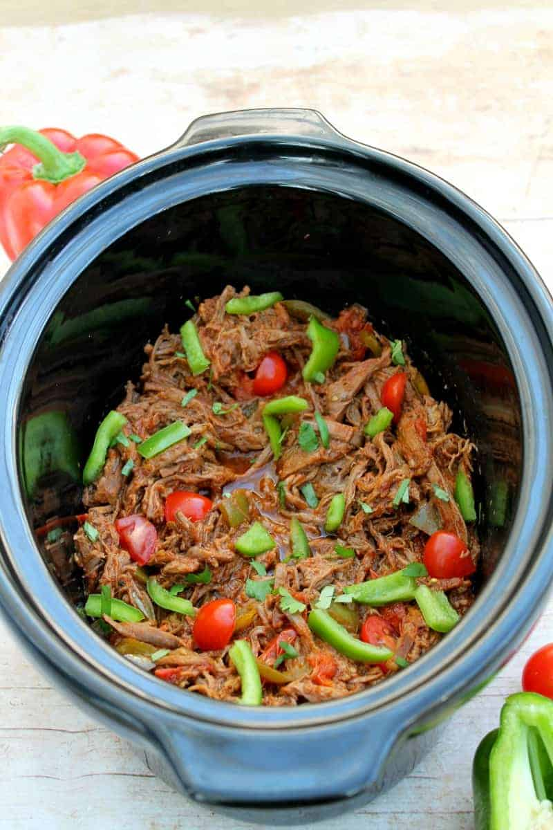 Shredded beef in a slow cooker pot with green peppers and tomatoes.