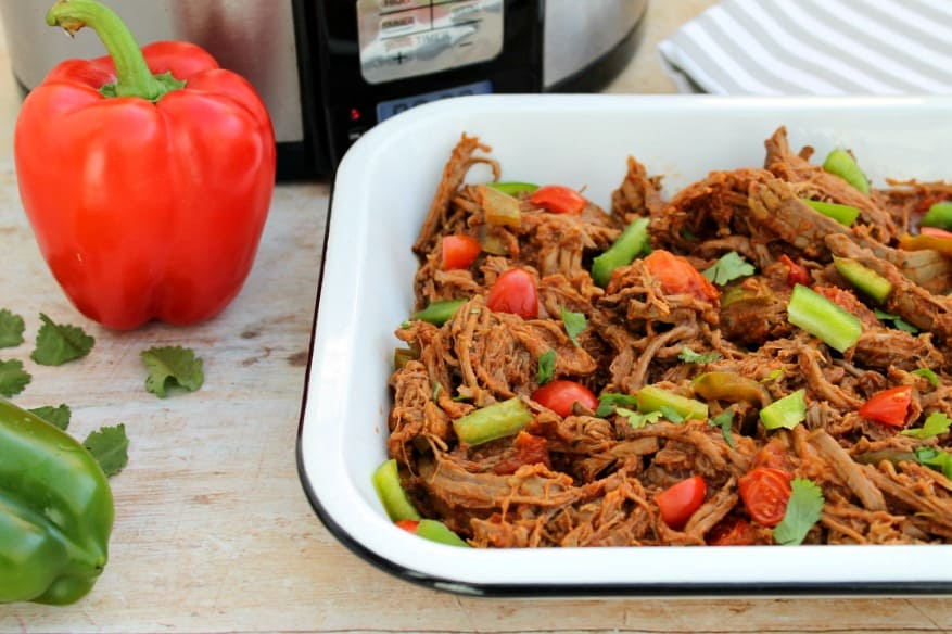 Shredded beef in a serving dish with crockpot behind and peppers on the table beside it.